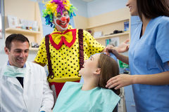 Clown in dental clinic make laugh young girl Royalty Free Stock Photo