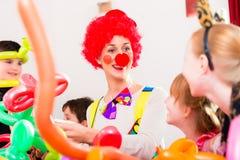 Clown an der Kindergeburtstagsfeier mit Kindern Stockbild