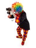 Clown, der mit Ferngläsern sucht Lizenzfreie Stockfotos