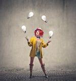 Clown, der mit Glühlampen spielt Stockfotografie