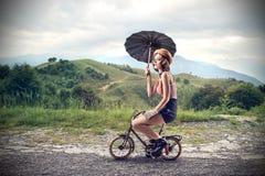 Clown die een kleine fiets met een paraplu berijden Stock Afbeelding