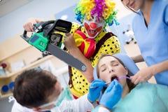 Clown do horror com a serra de cadeia na clínica dental imagens de stock
