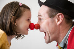 Clown doctor. Clown-doctor : red nose contact of clown with kid. Profiles of man and girl Stock Images