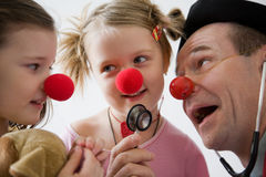 Clown doctor. Clown-doctor : two girls and clown with red noses are smiling and joking Royalty Free Stock Images