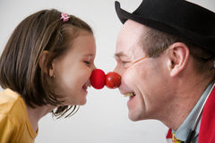 Clown doctor. Clown-doctor : red nose contact of clown with kid. Profiles of man and girl Stock Photos