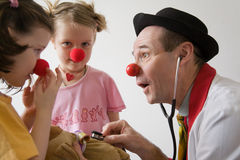 Clown doctor. Clown-doctor : two girls and clown with red noses are smiling and joking during medical examination of teddy bear Stock Images