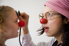 Clown doctor. Clown-doctor : girl and clown with red nose are smiling and joking during medical examination Royalty Free Stock Images
