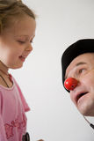 Clown doctor. Clown-doctor : girl and clown with red nose are smiling and joking during medical examination Stock Image