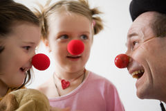 Clown doctor. Clown-doctor : two girls and clown with red noses are smiling and joking Stock Photography