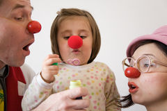 Clown doctor. Girl with two red nose clowns is blowing out bubbles Royalty Free Stock Photography