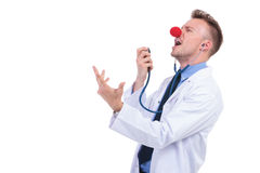 Clown doctor singing karaoke on his stethoscope. And having a good time Royalty Free Stock Image
