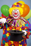Clown Does Magic Trick. Happy birthday clown does a magic trick with a top hat and wand Royalty Free Stock Photo