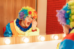 Clown does a make-up in front of the mirror. Royalty Free Stock Photography