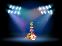 A clown doing some tricks at the center of the stage Royalty Free Stock Image