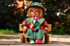 Clown doll on bench outdoors