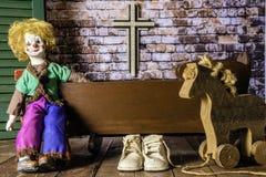 Clown Doll Rocking Baby in der Wiege Stockfoto