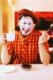 The clown is eating a cake in a cafe and his face is croaking. Mime eats cake in a cafe and croaks a face Stock Image