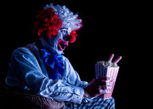 Clown eating popcorn. Colorful  clown with crazy expression eating popcorn watching a movie Royalty Free Stock Photography
