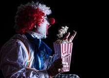 Clown eating popcorn. Clown throwing popcorn into his mouth while watching a movie Stock Photo