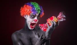 Clown effrayant avec le maquillage fantasmagorique et plus de sucrerie Image stock