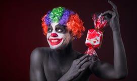 Clown effrayant avec le maquillage fantasmagorique et plus de sucrerie Images libres de droits