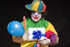 Clown et chapeau horribles sur la tête avec des présents et des sucreries à disposition Photos stock