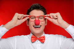 Clown in eyeglasses. Cheerful man with clown nose touching his e. Yeglasses while standing  on red Stock Photo