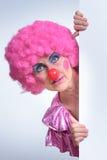 Clown féminin Peeking Out From derrière le papier d'affiche photo stock