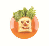 Clown face of a slice of bread, lettuce hair, red nose. Stock Photography