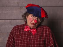 A clown with a facial expression of the unknowing. Clown with glasses, plaid shirt and beret with facial expressions on the face Royalty Free Stock Image