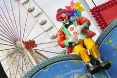 Clown and ferris wheel. Plastic clown and ferris wheel on a funfair royalty free stock image