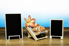 Clown fish on beach bed with flower and two blank back board. Isolated on gradient blue color background Stock Photo