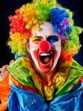 Clown fou sur le fond noir Portrait de femme folle Photographie stock