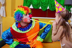 Clown and girl plays with tube on birthday party. Stock Photos