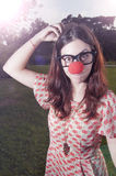 Clown girl with red nose at the park Stock Photo