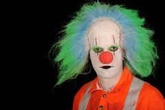 Clown with green hair. Portrait of male clown with green hair and fluorescent top, isolated on black background Stock Image
