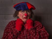 Clown with grimace annoyance, red nose clothes, beret. Emotional sad feminine clown with glasses, red shirt, nose and gloves blue hat, wooden background Royalty Free Stock Photo