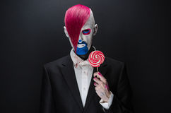 Clown and Halloween theme: Scary clown with pink hair in a black jacket with candy in hand on a dark background in the studio Stock Photography