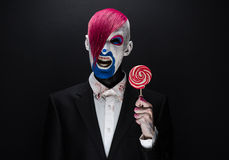 Clown and Halloween theme: Scary clown with pink hair in a black jacket with candy in hand on a dark background in the studio Stock Photo