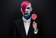 Clown and Halloween theme: Scary clown with pink hair in a black jacket with candy in hand on a dark background in the studio Stock Image