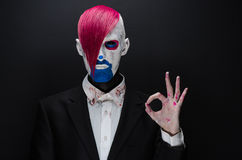 Clown and Halloween theme: Scary clown with pink hair in a black jacket with candy in hand on a dark background in the studio Royalty Free Stock Image