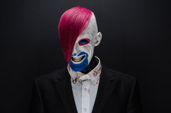Clown and Halloween theme: Scary clown with pink hair in a black jacket with candy in hand on a dark background in the studio Royalty Free Stock Photography