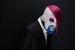 Clown and Halloween theme: Scary clown with pink hair in a black jacket with candy in hand on a dark background in the studio Stock Photos