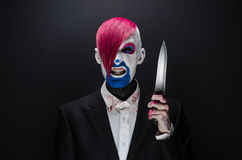 Clown and Halloween theme: Scary clown with pink hair in a black jacket with candy in hand on a dark background in the studio Royalty Free Stock Images
