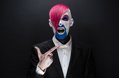 Clown and Halloween theme: Scary clown with pink hair in a black jacket with candy in hand on a dark background in the studio Royalty Free Stock Photos