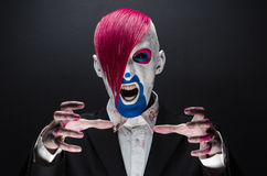 Clown and Halloween theme: Scary clown with pink hair in a black jacket with candy in hand on a dark background in the studio Stock Images