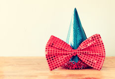 Clown hat and big bow tie over wooden table. filtered image. Stock Photos