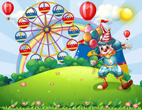 A clown at the hilltop with an amusement park and a rainbow Royalty Free Stock Photo