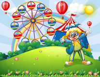 A clown at the hilltop with a carnival and a rainbow at the back Stock Images