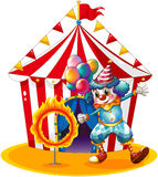 A clown holding balloons near the ring of fire stock illustration